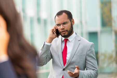 Confused Latin businessman calling on mobile phone while walking down city street. Man in office suit talking on cellphone outside. Phone talk concept 写真素材