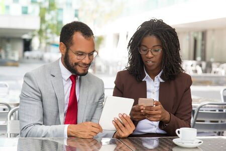 Cheerful colleagues discussing and checking reports on gadgets. Business man and woman sitting in coffee shop, showing tablet and smartphone screens to each other. Business discussion concept