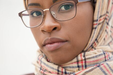 Serious face of Muslim woman in glasses posing outside. Closeup of smart young black business woman in hijab and office suit standing for camera. Confident Muslim woman concept