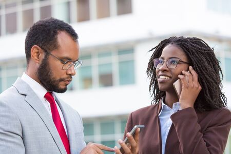 Diverse businesspeople using mobile phones outside. Business man texting message on smartphone, his colleague talking on cell. Digital devices concept