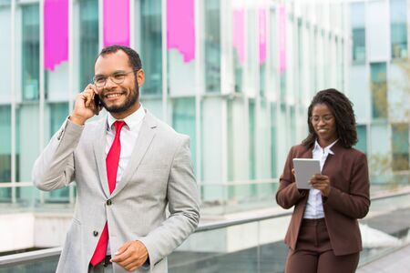 Happy Latin businessman talking on cellphone while walking down city street. Confident man in office suit calling on phone, city building and woman with tablet in background. Communication concept 写真素材