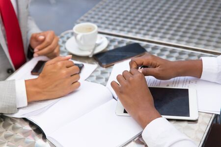 Business colleagues discussing contract in coffee shop. Closeup of business man and woman sitting at table with papers, gadgets, notebook with copy space, coffee cup. Business conversation concept