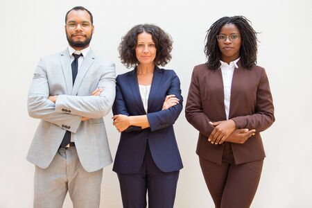 Successful diverse business team posing with arms folded. Business man and women standing over white background and looking at camera. Successful business people concept Фото со стока