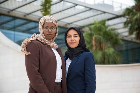 Confident proud female business team posing outside. Muslim women in hijabs and office suits standing close to each other and looking at camera. Successful businesswomen concept