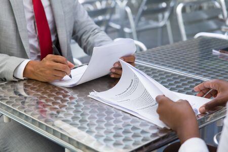 Business partners checking and signing documents in street cafe. Closeup of papers and writing business man hand. Deal or paperwork concept