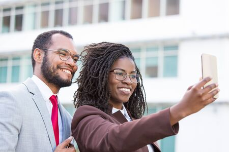Cheerful diverse business team taking selfie outside. Happy business man and woman holding smartphone, posing and smiling at screen. United team and selfie concept