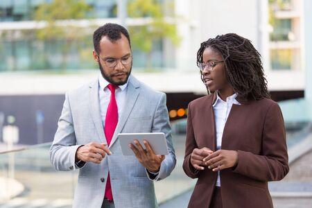 Multi-etnisch business team kijken naar presentatie op tablet op weg naar kantoor. Zakenman die tabletscherm toont aan zwarte vrouwelijke collega terwijl hij buiten loopt. Wi-Fi-verbindingsconcept Stockfoto