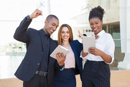 Cheerful business colleagues with tablets rejoicing at team success. Happy business man and women looking at tablet screen and making winner gesture. Successful teamwork concept