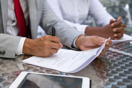 Businessman signing cost sheet or financial report. Closeup of document and business man hand writing with pen. Signature concept Stockfoto