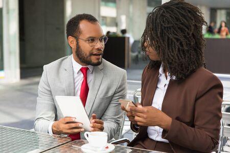 Colleghi di lavoro eccitati che discutono del progetto in un caffè di strada. Uomo d'affari e donna seduti in una caffetteria, utilizzando tablet e smartphone e parlando. Concetto di tecnologia digitale