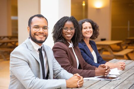 Happy diverse business team posing in street cafe. Business man and women with clasped hands sitting at table outside, looking at camera and smiling. Successful team concept