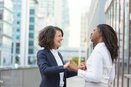 Joyful happy female colleagues celebrating team success outside. Business women standing in city street, laughing, talking and holding hands. Meeting or good news concept