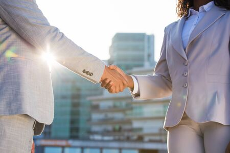 Business partners meeting in city in early morning. Business man and woman shaking hands in sunlight. Urban buildings in background. Corporate meeting concept