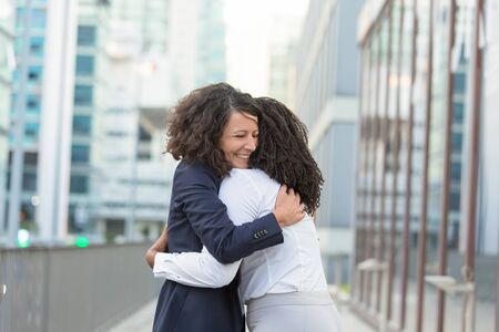 Old female friends glad to see each other outside. Business women standing in city street and hugging. Meeting and joy concept Stock Photo