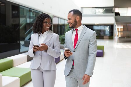 Happy business colleagues using mobile phones and chatting. Business man and woman walking through office hallway, holding smartphones and talking. Corporate communication concept Stock Photo