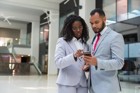 Focused business colleagues with smartphone. Confident young African American business people standing together and using mobile phone. Technology concept Stock Photo