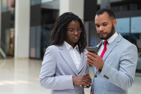 Focused businessman and businesswoman with smartphone. Confident young African American business people standing together and using mobile phone. Technology concept Stock Photo
