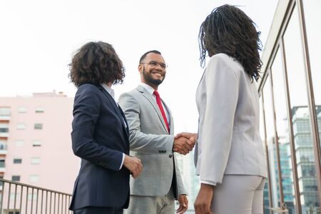 Friendly colleagues greeting each other near office building. Business man and women standing in city street and shaking hands. Corporate communication concept