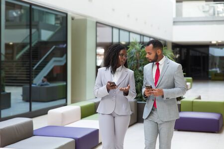 Diverse business professionals using mobile phones and discussing work issues. Business man and woman standing ib office hallway, holding smartphones and talking. Corporate communication concept