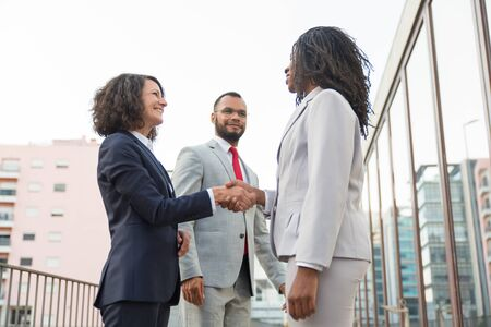 Happy confident business partners meeting near office building. Business man and women standing in city street and shaking hands. Contract concept
