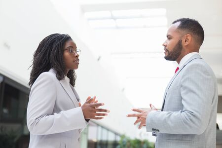 Serious excited business partners arguing about deal in office hall. Business man and woman standing in hallway, talking and gesturing. Negotiation concept