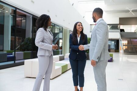 Happy friendly businesswoman welcoming partners in hallway. Business man and women standing in office hall, shaking hands with each other, talking and smiling. Diverse partners concept Stock Photo