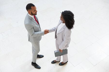 Diverse business partners greeting each other in office hallway. Business man and woman standing and shaking hands. Partnership concept