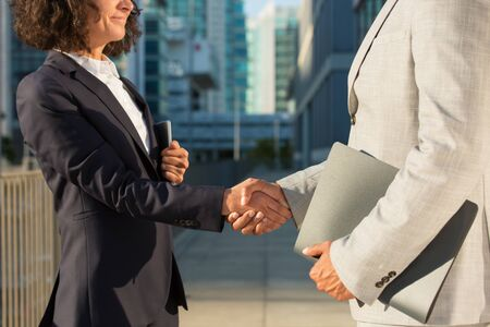 Businesspeople with documents meeting outside. Business man and woman holding folders and shaking hands. Business meeting concept Stock Photo