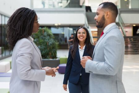 Happy successful company representative meeting customers in office hall. Young business woman smiling and walking to diverse business couple. Partnership concept Stock Photo