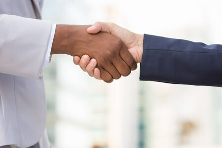 Diverse female business leaders shaking hands. Multiethnic business women in office suits greeting each other. Partnership concept Stock Photo