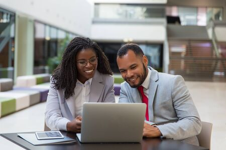Smiling business colleagues using laptop. Cheerful young African American business people sitting at table and using digital devices. Technology concept