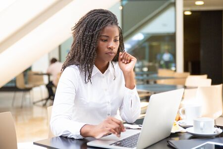 Focused female office worker using computer in coffee shop. African American business woman working on laptop in cafe and looking away. Internet technology concept Imagens