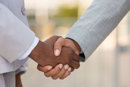 Mix raced business partners shaking hands outside. Diverse business people in office suits greeting each other. Collaboration concept Stock Photo
