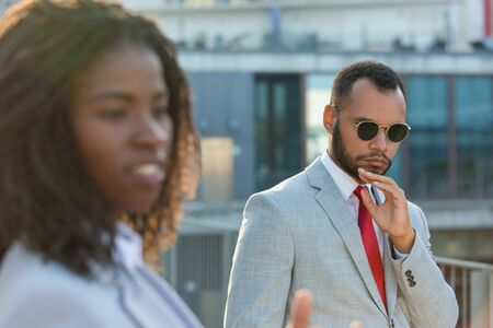 Serious businessman walking outside by his female colleague. Business man in formal suit and sunglasses standing near office building and posing for camera. Businesspeople outside concept Stock Photo