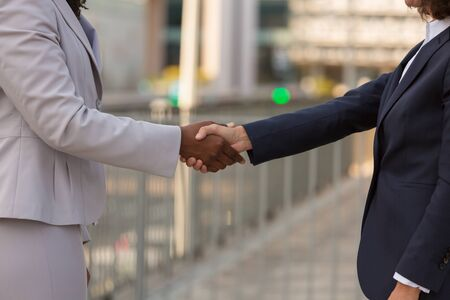 Businesswomen shaking hands with each other. Closeup of handshake of Caucasian and African American business ladies. Multiethnic partnership concept