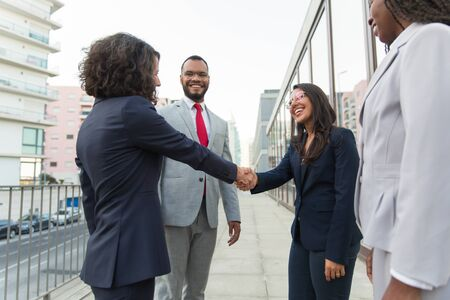 Happy female manager welcoming partners outside. Business man and women standing in city street, smiling, talking and shaking hands. Welcoming concept