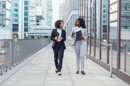 Businesswomen walking and talking on street. Professional multiethnic female colleagues holding folders, walking and talking outside office building. Teamwork concept