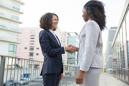 Happy diverse female business partners greeting each other outside. Successful business women standing near city building and shaking hands. Friendly handshake concept