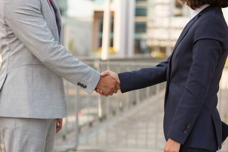 Business man and woman greeting each other outside. Business people shaking hands, urban buildings in background. Corporate communication concept