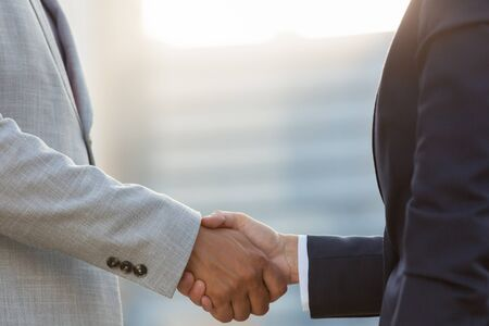Business partners shaking hands in morning sunlight. Business man and woman in office suits greeting each other. Partnership concept