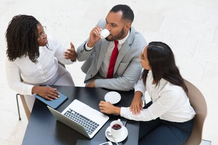 Diverse business colleagues drinking coffee while discussing project. Business man and women sitting at table with laptop and cups and talking. Business communication concept. Stock Photo