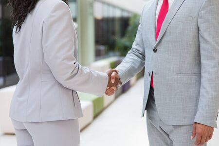 Closeup of handshake. Diverse business man and woman standing in office hallway and shaking hands. Agreement or deal concept