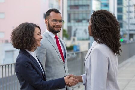 Happy friendly business colleagues greeting each other. Business man and women standing near city building, shaking hands, smiling and talking. Agreement concept