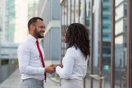 Happy old friends meeting outside and sharing good news. Business man and woman standing in city street, holding hands, smiling and talking. Friends meeting concept Stock Photo