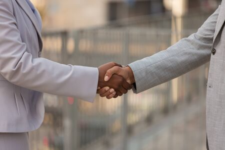 Closeup of handshake. Business man and woman in office suits shaking hands. Dealing concept Standard-Bild