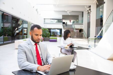 Serious confident entrepreneur using laptop in office building hall. Business man sitting at table, working on computer, young woman using gadget in background. Wi-Fi concept
