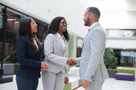 Happy joyful diverse business partners greeting each other in hallway. Business man and women standing, shaking hands with each other, talking and smiling. Successful partnership concept Stock Photo