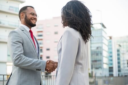 Friendly diverse business colleagues glad to see each other. Business man and woman standing outside and shaking hands. Corporate meeting concept Stock Photo