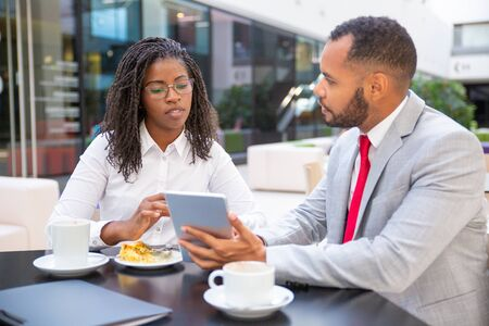 Multiethnic business colleagues watching and discussing content on tablet. Business man and woman sitting in cafe, using tablet together and talking. Wi-Fi concept Stock Photo
