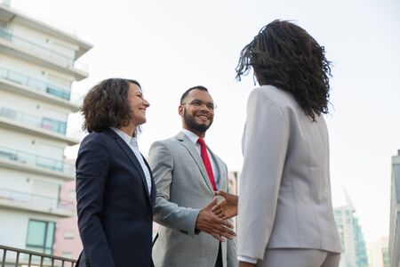 Group of confident business partners greeting each other outside. Business man and women standing near urban buildings and shaking hands. Partnership concept